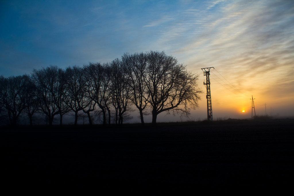 Sonnenaufgang mit Strommast